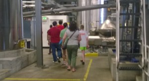 "Alex (in ""Staff"" shirt and neon shorts) during the brew tour.  Blurry because I was walking and snapping the pic, and the phone camera is no good at that."